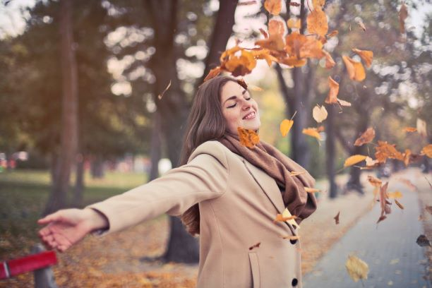A woman throwing Autumn leaves on herself