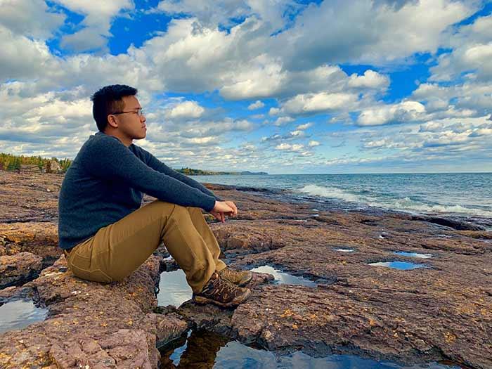 A man sitting calming by a lake