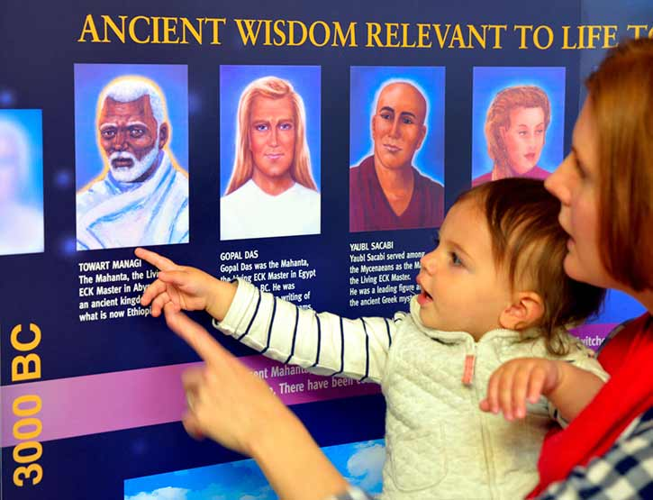 A mother and small child pointing at the spiritual teachers on an Eckankar display