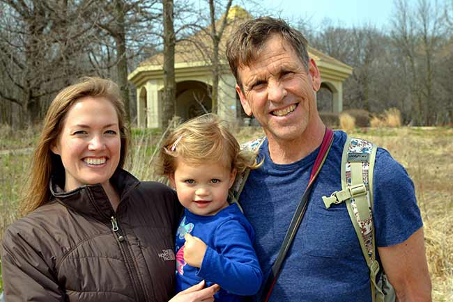 Two parents with their toddler smiling outdoors