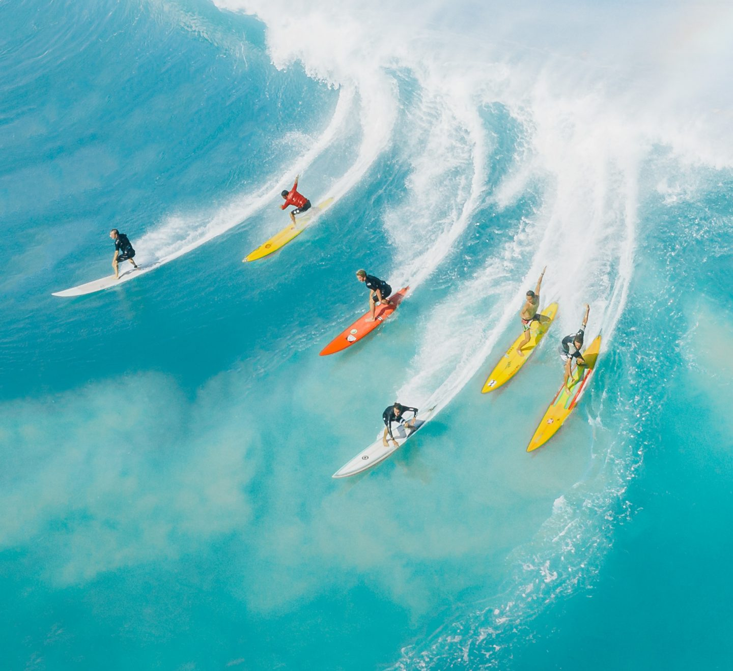 Several people surfing on a big wave