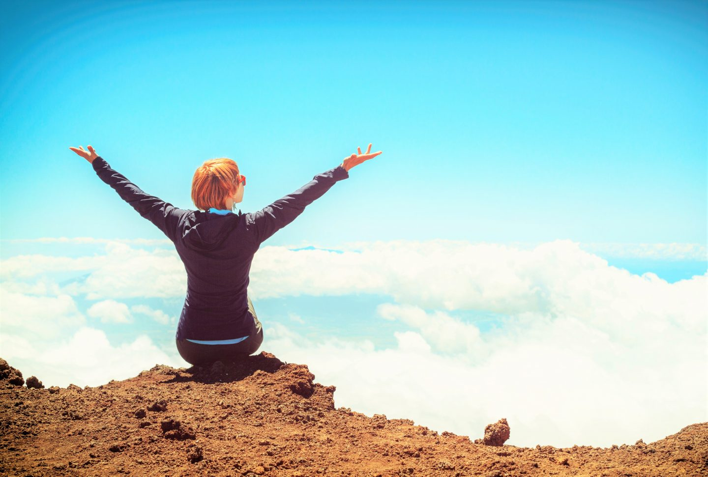 A woman sitting on top of a cliff looking out at the sky with her arms held up towards it.
