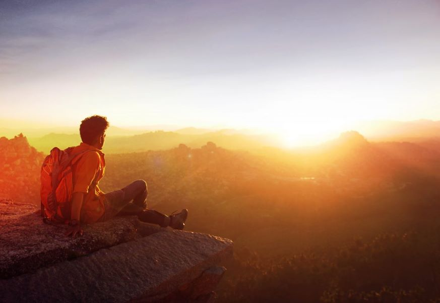 A person watching the sun rise over mountains